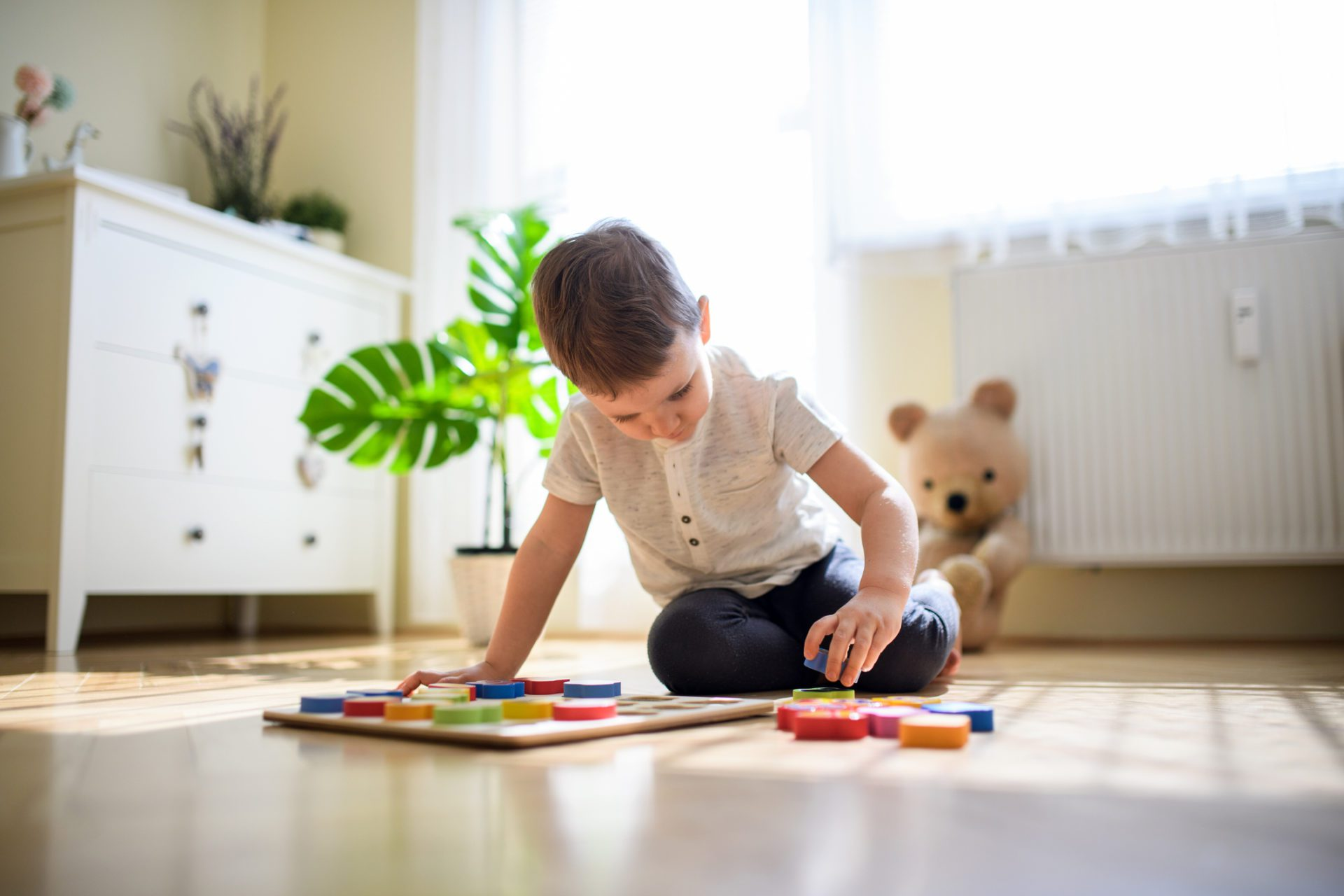 Small boy indoors at home, playing on floor.