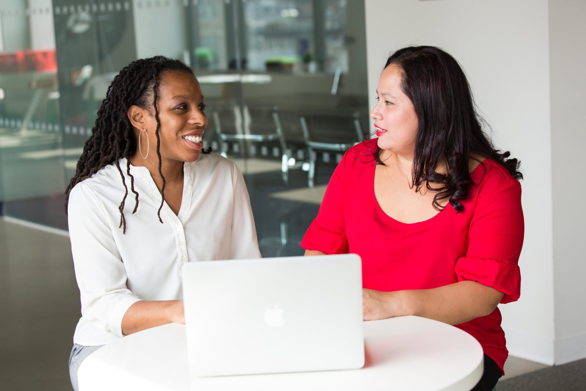 two women talking with laptop
